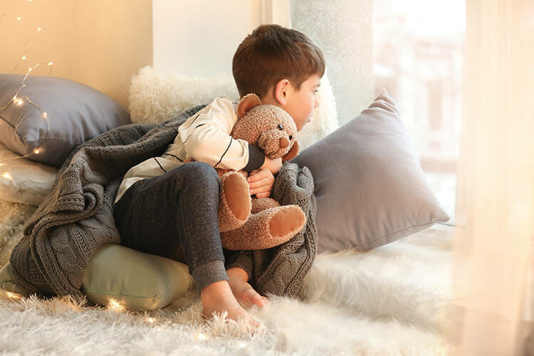 Cute little boy with teddy bear near window at home