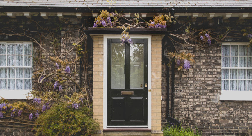 black-front-door-with-glazing-on-beautiful-stone-house