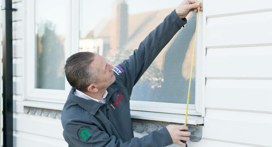 Staff-measuring-space-for-replacement-windows