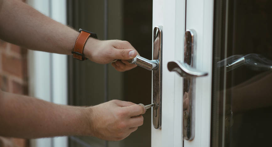 man-locking-patio-door-with-key